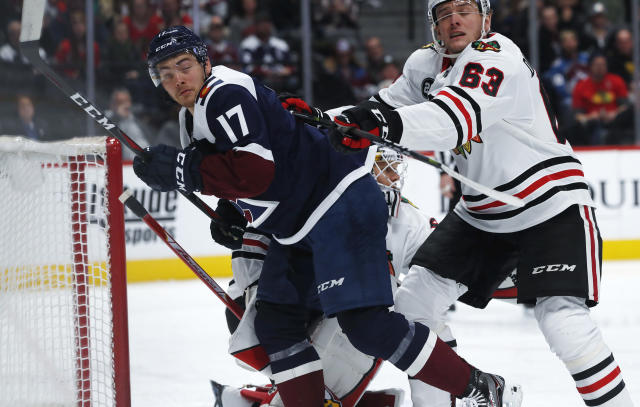 Chicago Blackhawks defenseman Carl Dahlstrom, right, clears Colorado Avalanche center Tyson Jost out from in front of the net in the first period of an NHL hockey game Saturday, Dec. 29, 2018, in Denver. (AP Photo/David Zalubowski)