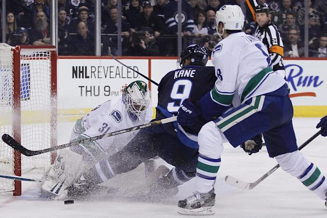 Vancouver Canucks' Christopher Tanev (8) defends Winnipeg Jets' Evander Kane (9) in front of goaltender Eddie Lack (31) during the second period of an NHL hockey game Wednesday, March 12, 2014, in Winnipeg, Manitoba. Kane was awarded a penalty shot on the play. (AP Photo/The Canadian Press, John Woods)