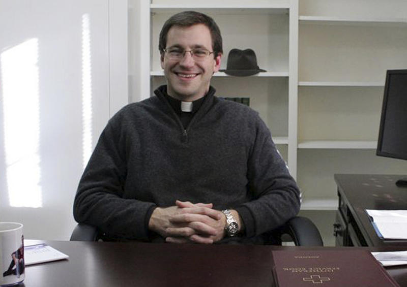 In this January 2012 photo provided by the Newtown Bee, the Rev. Rob Morris sits in his office at Christ the King Lutheran Church in Newtown, Conn.  The Lutheran Church-Missouri Synod denomination is reprimanding Rev. Morris for participating  in an interfaith vigil on Dec. 16, 2012, after the Sandy Hook massacre. The denomination bars joint worship because it doesn't want to appear to mix its beliefs with those of other faiths. (AP Photo/Newtown Bee, Shannon Hicks)