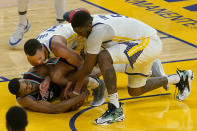 Memphis Grizzlies guard De'Anthony Melton, bottom, wrestles for the ball under Golden State Warriors guard Stephen Curry, middle, and center Kevon Looney (5) during the second half of an NBA basketball game in San Francisco, Sunday, May 16, 2021. (AP Photo/Jeff Chiu)