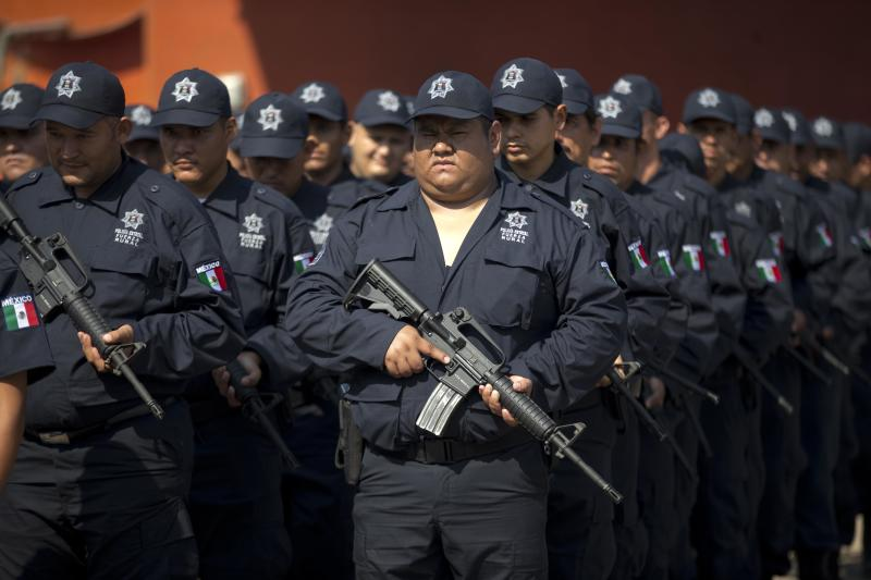 In this May 10, 2014 photo, Self-defense group members stand in their newly-issued uniforms before the start of a ceremony in Tepalcatepec, Mexico. At the ceremony in the town where the vigilante movement began in February 2013, officials handed out new pistols, rifles and uniforms to 120 self-defense group members who were sworn into a new official rural police force. Mexico's government on Saturday began demobilizing the vigilante movement of assault-rifle-wielding ranchers and farmers that had succeeded in largely expelling the Knights Templar cartel from the western state of Michoacan when authorities couldn't. (AP Photo/Eduardo Verdugo)