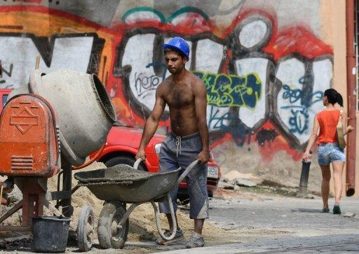 A construction worker works pushes a wheelbarrow in Bucharest on August 10. The recovery in Romania's economy after two years of severe recession is now coming under threat, analysts warn, victim to the months-long political crisis that has engulfed the EU country
