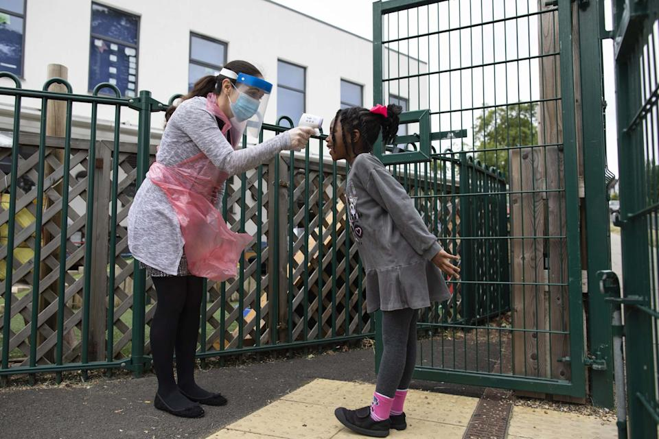 Trial run: a member of staff takes a girl's temperature at Harris Academy Shortlands in June. Ministers have promised all schools in England will open in four weeks' time: Getty Images