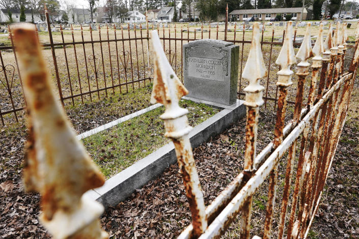 A rusted fence surrounds a tombstones at the Lincoln Memorial Cemetery in Portsmouth, Va., Tuesday, March 23, 2021. Many Black Americans excluded from white-owned cemeteries built their own burial spaces, and their descendants are working to preserve the grounds. Racism still haunts these cemeteries, though. Many are at risk of being lost and lack the support other cemeteries have received. (AP Photo/Steve Helber)