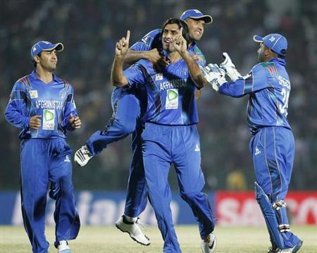 Afghanistan's fielders congratulate bowler Zadran as for dismissing Bangladesh's Rahman successfully during their one-day international cricket match at the Asia Cup 2014 in Fatullah