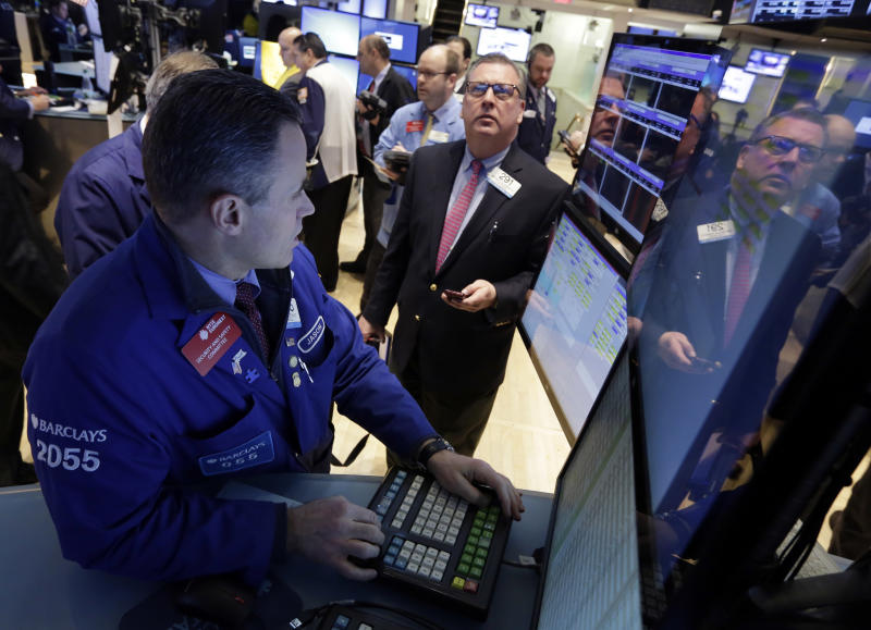 Jason Hardzewicz, left, works at his post on the floor of the New York Stock Exchange, Monday, Jan. 27, 2014. Stocks are mostly higher on Wall Street as investors shrug off worries about emerging markets that tanked the market last week. (AP Photo/Richard Drew)