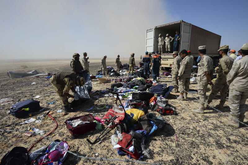 FILE - In this file photo taken onFILE - In this Monday, Nov. 2, 2015 file photo provided by the Russian Ministry for Emergency Situations, Egyptian soldiers collect personal belongings of plane crash victims at the crash site of a passenger plane bound for St. Petersburg in Russia that crashed in Hassana, Egypt's Sinai Peninsula. Russia's transportation minister said Friday, Dec. 15, 2017 flights between Moscow and the Egyptian capital of Cairo are to resume in February after a two-year hiatus. Moscow suspended flights to Egypt after an Islamic State bomb brought down a Russian airliner over Sinai in October 2015, killing all 224 people on board. (Russian Ministry for Emergency Situations via AP, File)