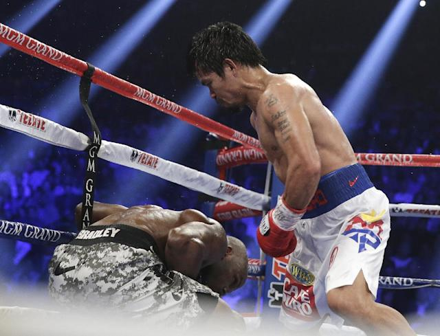 Manny Pacquiao, right, of the Philippines, drives Timothy Bradley down into the ropes in their WBO welterweight title boxing bout Saturday, April 12, 2014, in Las Vegas. (AP Photo/Isaac Brekken)