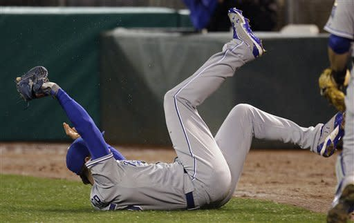 Kansas City Royals first baseman Eric Hosmer slides while making the catch on a fly ball hit by Oakland Athletics' Coco Crisp during the first inning of a baseball game Tuesday, April 10, 2012, in Oakland, Calif. (AP Photo/Ben Margot)