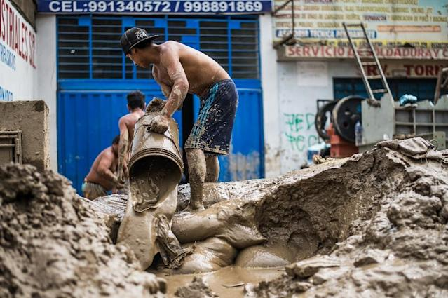 Residents of a populous district of Lima remove from their house mud, debris and water left by a flash flood, on March 19, 2017 (AFP Photo/ERNESTO BENAVIDES)