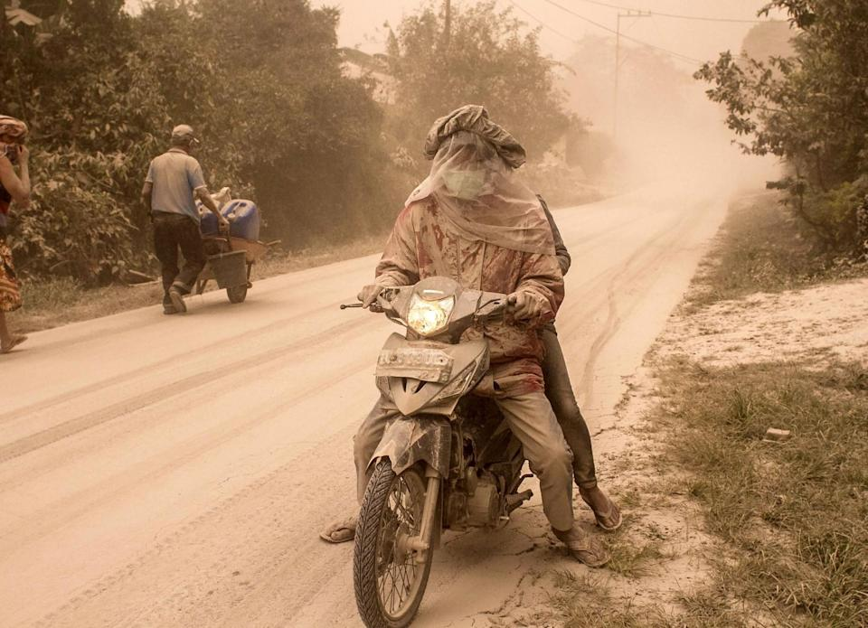 <p>A man drives his motorbike through thick dust during the eruption of Mount Sinabung in Indonesia. (Rex features) </p>