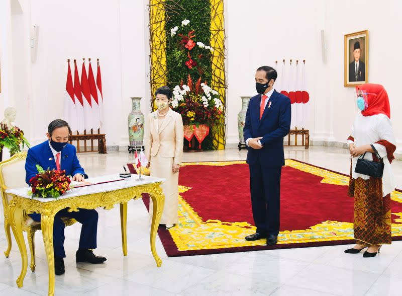 Japan's PM Suga signs guest book at Indonesian Presidential Palace in Bogor
