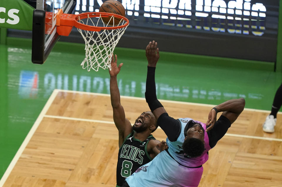 Boston Celtics' Kemba Walker, left, shoots at the basket as Miami Heat's Bam Adebayo, right, tries to block in the first half of a basketball game, Sunday, May 9, 2021, in Boston. (AP Photo/Steven Senne)