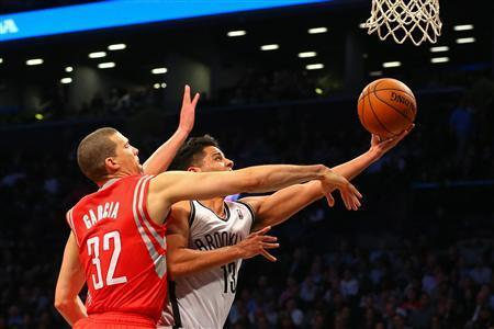 Apr 1, 2014; Brooklyn, NY, USA; Brooklyn Nets guard Jorge Gutierrez (13) shoots the ball while being defended by Houston Rockets guard Francisco Garcia (32) during the fourth quarter at Barclays Center. The Nets defeated the Rockets 105-96. Mandatory Credit: Ed Mulholland-USA TODAY Sports