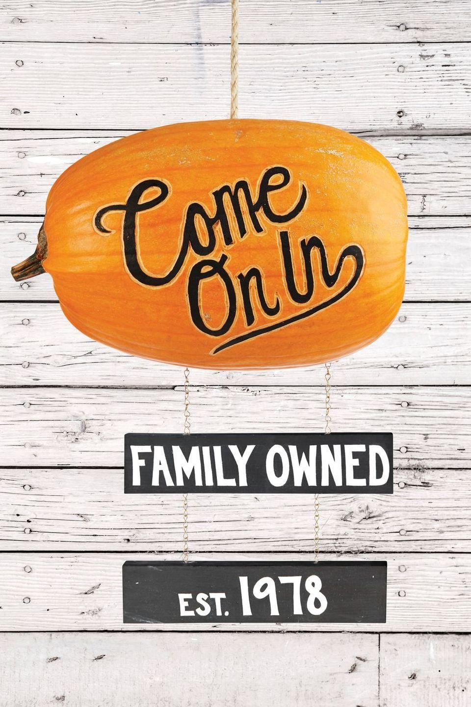 "<p>Welcome guests with a custom pumpkin sign. Customize as desired by writing your family name, the year your house was built, or festive spooking sayings.</p><p><strong>Make the Pumpkin Sign:</strong> Cut a large hole in back of an oblong pumpkin; scoop out pulp and seeds. Remove flesh so it's light enough to hang. Etch outline of desired phrase on long side of pumpkin. Color center of letters with a black oil-based paint pen. Paint two 2"" by 1"" boards black; once dry, use white paint for desired phrases. Hang from bottom of pumpkin with chain. Cut hole in oblong top of pumpkin. Cut 1"" dowel the width of the top inside of pumpkin (parallel with words). Tie <a href=""https://www.amazon.com/Lehigh-Group-530X-Twine-Heavy/dp/B000VYBB0I?linkCode=ogi&tag=countryliving_auto-append-20&ascsubtag=[artid