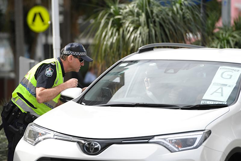 A police officer stops a motorist at a border check.