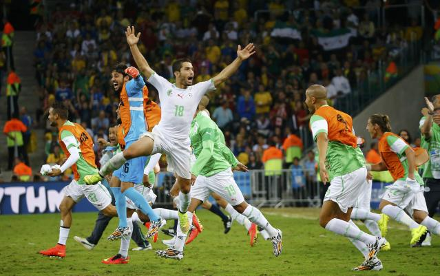 Algeria's Abdelmoumene Djabou (C) celebrates with his teammates at the end of their 2014 World Cup Group H soccer match against Russia at the Baixada arena in Curitiba June 26, 2014. REUTERS/Murad Sezer (BRAZIL - Tags: SOCCER SPORT WORLD CUP TPX IMAGES OF THE DAY)