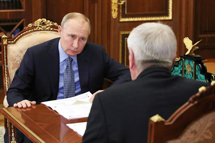 Russian President Vladimir Putin, seated in an ornate chair with hands on a wooden table, leans forward and scowls at head of Russia's Federal Service for Financial Monitoring Yuri Chikhanchin, seated across from him and seen from behind