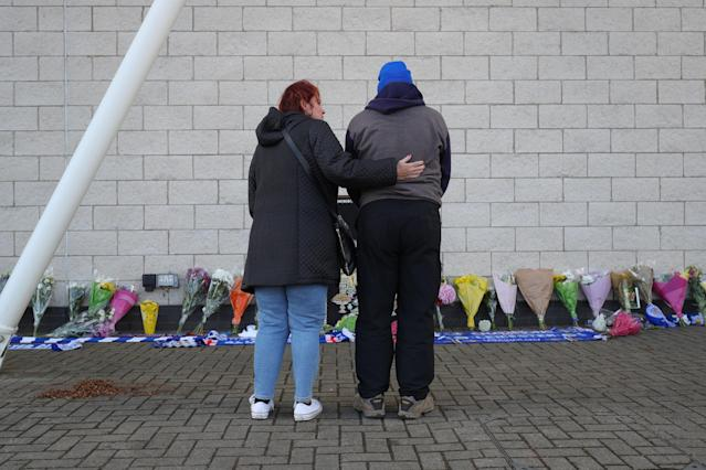 <p>Supporters looking at the tributes to the Leicester City owner after the horrifying crash. Aaron Chown/PA Wire </p>