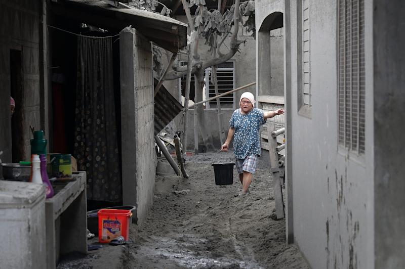 A resident fetches water at their volcanic ash covered village in Laurel, Batangas province.