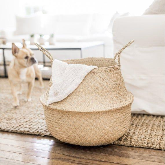 """<p><strong>SonaHome</strong></p><p>etsy.com</p><p><strong>$27.00</strong></p><p><a href=""""https://go.redirectingat.com?id=74968X1596630&url=https%3A%2F%2Fwww.etsy.com%2Flisting%2F716564212%2Fwoven-natural-seagrass-storage-basket&sref=https%3A%2F%2Fwww.thepioneerwoman.com%2Fhome-lifestyle%2Fdecorating-ideas%2Fg35001978%2Fblanket-storage-ideas%2F"""" rel=""""nofollow noopener"""" target=""""_blank"""" data-ylk=""""slk:Shop Now"""" class=""""link rapid-noclick-resp"""">Shop Now</a></p><p>This classic belly basket allows you to keep all your beloved blankets nearby. Just fold them or roll and stack them inside. </p>"""