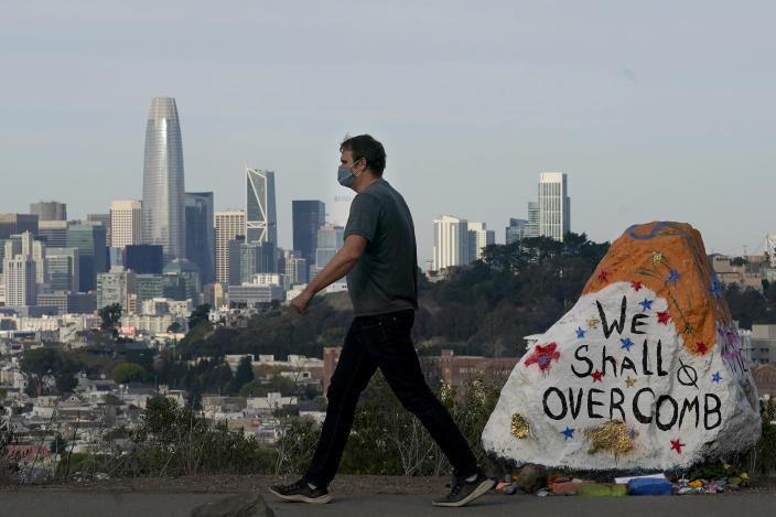 A man wears a mask as he walks past a painted rock on Bernal Heights in front of the skyline during the coronavirus outbreak in San Francisco, Saturday, Nov. 21, 2020. (AP Photo/Jeff Chiu)