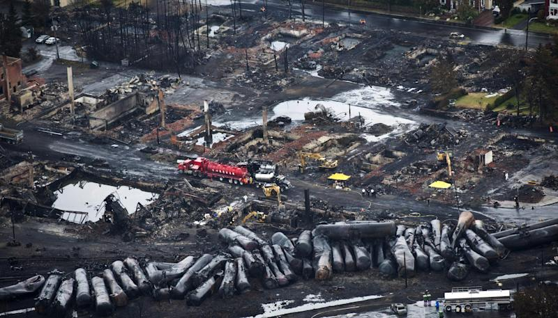 FILE - In this July 9, 2013, file photo, workers comb through debris after an oil train derailed and exploded in the town of Lac-Megantic, Quebec, killing 47 people. In response to Lac-Megantic, the National Transportation Safety Board and Transportation Safety Board of Canada in January 2014, called on regulators to require railroads to take stock of the risks along certain oil train routes and change them if needed. (AP Photo/The Canadian Press, Paul Chiasson, File)