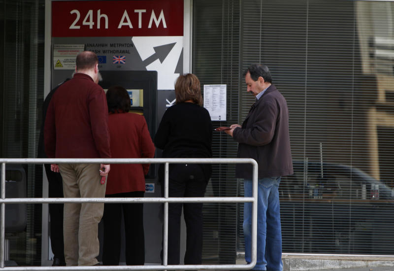 People use the ATM of a closed branch of Laiki Bank in capital Nicosia, Thursday, March 21, 2013. The European Central Bank says it will keep emergency aid for Cyprus' troubled banks in place at least until Monday but will have to cut it off after that unless an international rescue program is drawn up. (AP Photo/Petros Karadjias)