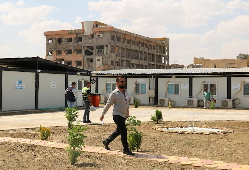 A man walks in front of pre-fabricated units at the newly re-opened al-Jamhuri hospital in the northern city of Mosul on September 9, 2018 (AFP Photo/Waleed AL-KHALID)