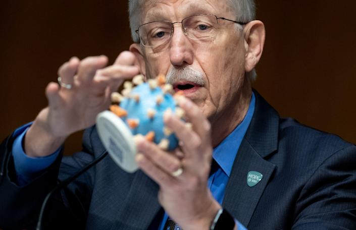Dr. Francis Collins, Director of the US National Institutes of Health, holds up a model of the novel coronavirus during a US Senate Appropriations subcommittee hearing on the plan to research, manufacture and distribute a coronavirus vaccine on July 2, 2020.