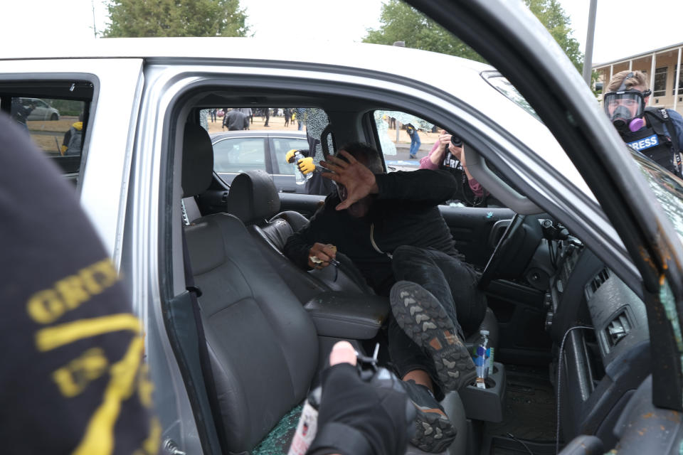 This Sunday, Aug. 22, 2021 photo, an anti-fascist protester holds up their hand after members of the far-right group Proud Boys physically assaulted them in a vehicle after smashing every window and popping all four tires during clashes between the politically opposed groups in Portland, Ore. Police in Portland have been criticized that they did little to prevent violent clashes between right- and left-wing protesters on Sunday. (AP Photo/Alex Milan Tracy)