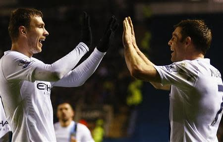 Manchester City's Edin Dzeko (L) celebrates his goal against Leicester City with James Milner during their English League Cup quarter-final soccer match at the King Power stadium in Leicester, central England, December 17, 2013. REUTERS/Darren Staples