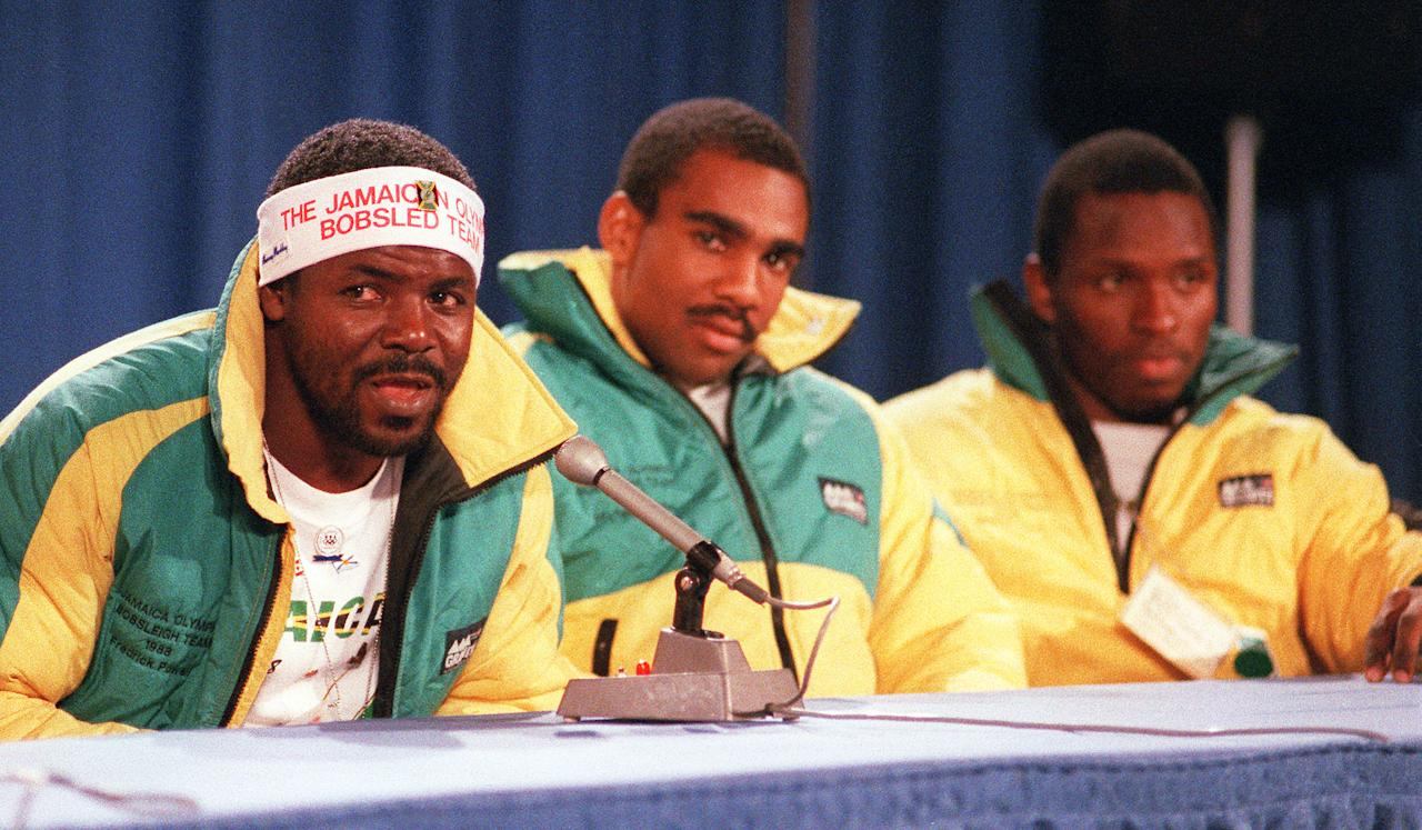 <p>Jamaica's Frederick Powell speaks during a press conference as his teammates Michael White and Allen Caswell listen on the eve of the opening of the 1988 Winter Olympic Games in Calgary. (Getty Images) </p>
