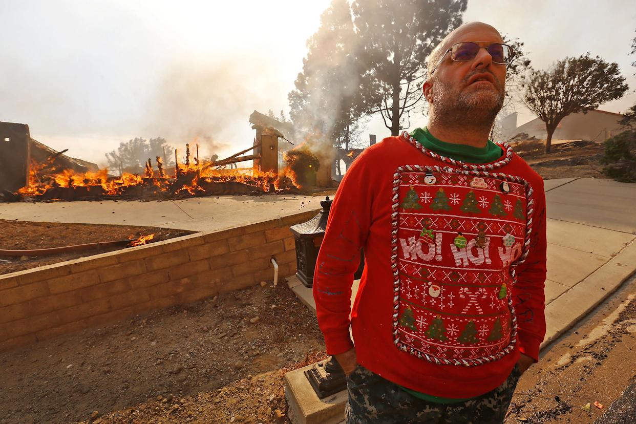 Wearing his Christmas garb, Justin Ekback stands in front of one of the multi-million dollar homes destroyed in Ventura County by a wildfire on Dec. 5.
