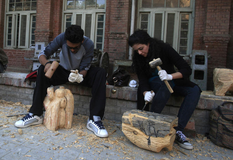 In this photo taken on Tuesday, Dec. 6, 2012, Pakistani students carve wooden statues in the National College of Arts in Lahore, Pakistan. A series of provocative paintings of Muslim clerics in scenes suggesting homosexuality has sparked a moral and legal crisis at Pakistan's leading arts college after extremists threatened violence, declaring that the works insult Islam.(AP Photo/K.M. Chaudary)