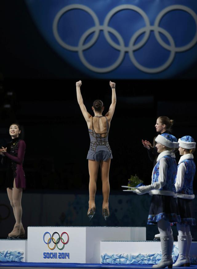 First-placed Russia's Adelina Sotnikova (C), second-placed South Korea's Kim Yuna (L) and third-placed Italy's Carolina Kostner celebrate on the podium after the figure skating women's free skating program at the 2014 Sochi Winter Olympics, February 20, 2014. REUTERS/Lucy Nicholson (RUSSIA - Tags: OLYMPICS SPORT FIGURE SKATING)