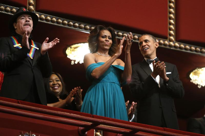 U.S. President Barack Obama, first lady Michelle Obama and Carlos Santana applaud in their box during the Kennedy Center Honors in Washington