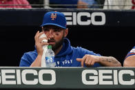 A night after being hit in the face with a fast ball New York Mets' Kevin Pillar holds an ice pack to his face as he watches from the during a baseball game Tuesday, May 18, 2021, in Atlanta. (AP Photo/John Bazemore)