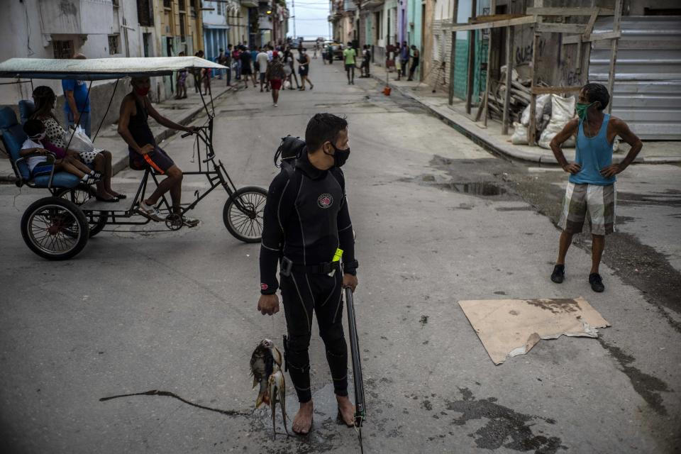 Wearing a face mask amid the new coronavirus pandemic, diver Yuniel Gonzalez walks home with his catch of the day, in Havana, Cuba, Tuesday, Oct. 27, 2020. A Trump reelection would likely spell another four years of tightened U.S. sanctions while many expect a Biden administration to carry out at least some opening. (AP Photo/Ramon Espinosa)
