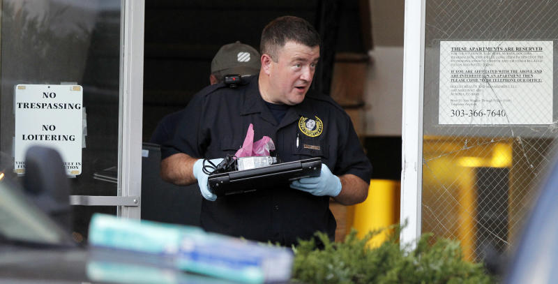 "Investigators remove computer equipment as evidence from the apartment of alleged gunman James Holmes, Saturday, July 21, 2012 in Aurora, Colo. Authorities reported that 12 died and more than three dozen people were shot during an assault at a movie theatre midnight premiere of ""The Dark Knight Rises."" (AP Photo/Alex Brandon)"