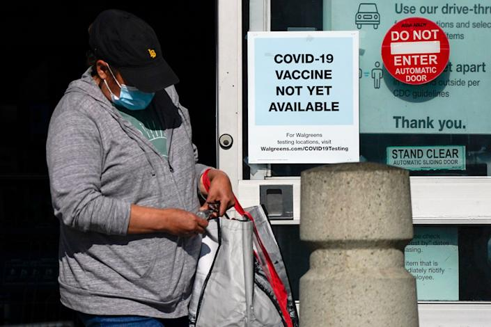 A customer walks past a sign indicating that a COVID-19 vaccine is not yet available at Walgreens, Wednesday, Dec. 2, 2020, in Long Beach, Calif.