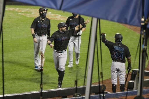 Miami Marlins' Francisco Cervelli celebrates with teammates after hitting a three-run home run during the second inning of a baseball game against the New York Mets Friday, Aug. 7, 2020, in New York. (AP Photo/Frank Franklin II)