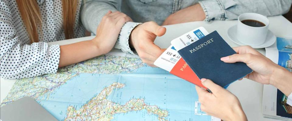 Young couple in a tour agency communication with a travel agent travelling concept passports and tickets