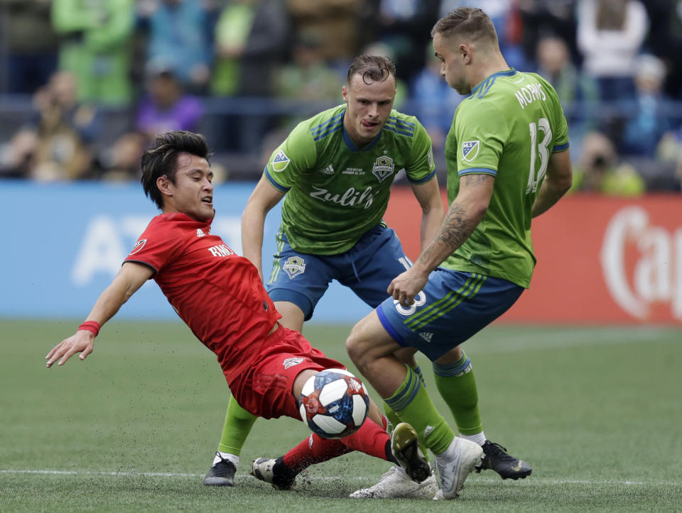 Toronto FC's Tsubasa Endoh, left, battles for a ball with Seattle Sounders' Jordan Morris, right, Sunday, Nov. 10, 2019, during the first half of the MLS Cup championship soccer match in Seattle. (AP Photo/Elaine Thompson)