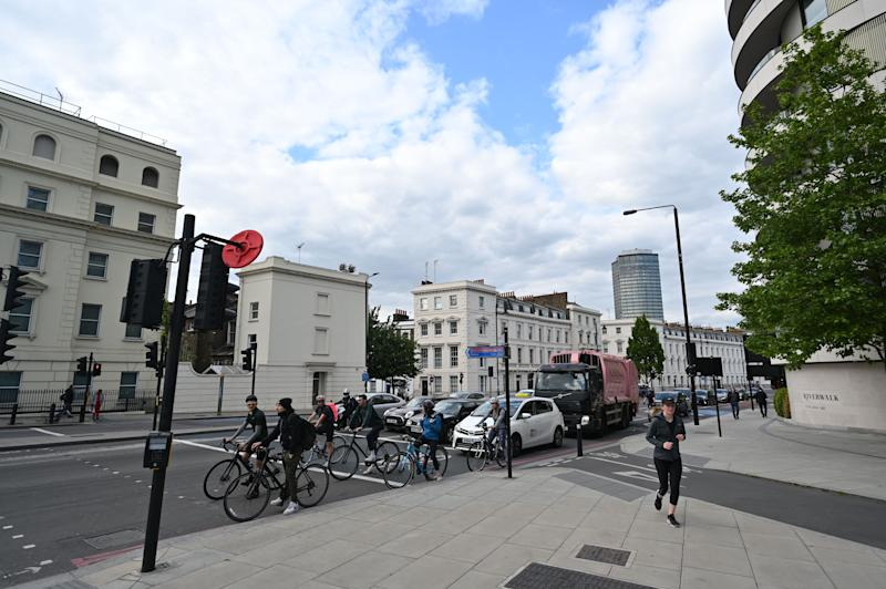 """People on bicycles wait in front of traffic on a road in London on May 12, 2020, during the novel coronavirus COVID-19 pandemic. - The British government on Monday published what it said was a """"cautious roadmap"""" to ease the seven-week coronavirus lockdown in England, notably recommending people wear facemasks in some public settings. (Photo by JUSTIN TALLIS / AFP) (Photo by JUSTIN TALLIS/AFP via Getty Images)"""