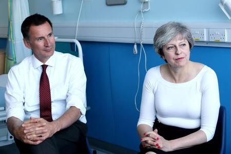 FILE PHOTO: Britain's Prime Minister Theresa May (R) and Secretary of State for Health Jeremy Hunt speak to patients during a round table discussion as they visit the Renal Transplant Unit at the Royal Liverpool University Hospital, Liverpool, Britain, October 12, 2017. REUTERS/Christopher Furlong/Pool