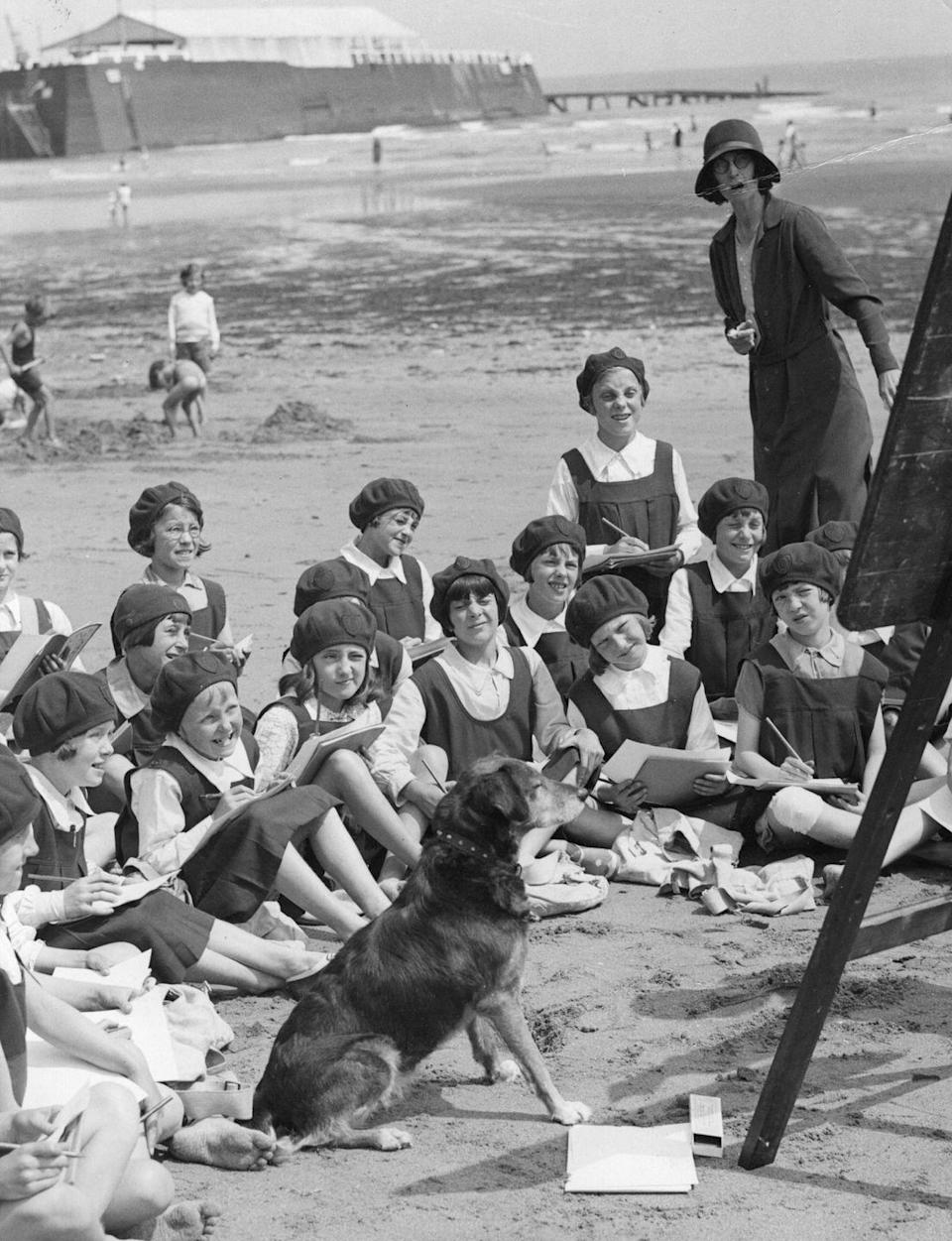 <p>A group of girls enjoy an outdoor painting class while on a school trip to the beach. </p>