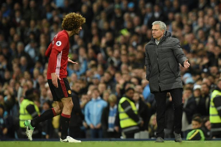 Manchester United's midfielder Marouane Fellaini (L) reacts to Manchester United's manager Jose Mourinho (R) as he leaves the pitch after being sent off during the English Premier April 27, 2017