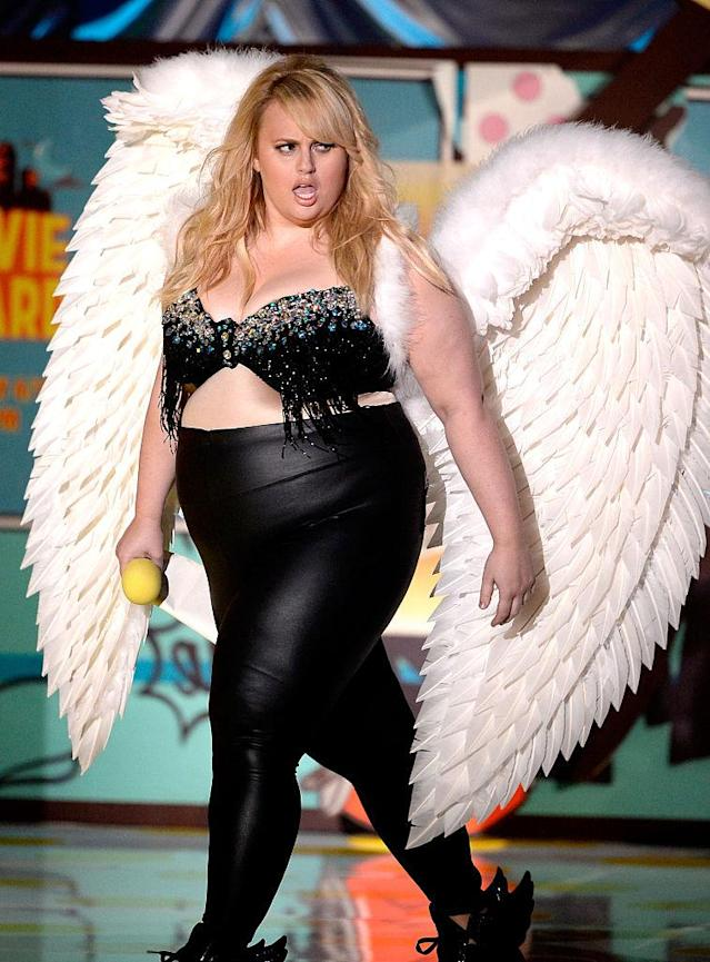 """Rebel Wilson took a public jab at Victoria's Secret while hosting the 2015 MTV Movie Awards wearing angel wings and leather pants with """"Think"""" encrusted across her bottom. (Photo: Getty Images)"""