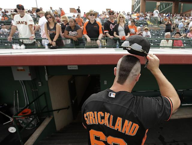 San Francisco Giants relief pitcher Hunter Strickland shows off his haircut to fans before a spring training baseball game against the Cincinnati Reds in Scottsdale, Ariz., Thursday, March 6, 2014. (AP Photo/Chris Carlson)